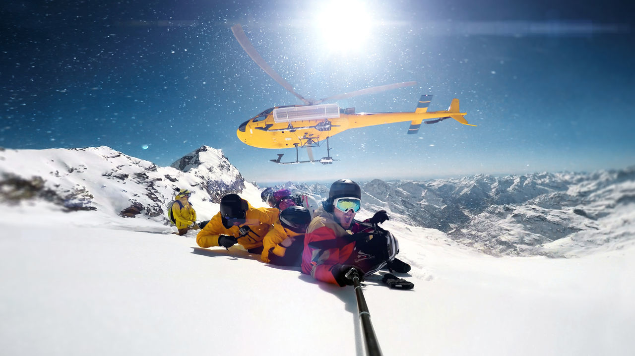 People snowboarding on snowcapped mountain against helicopter flying in sky