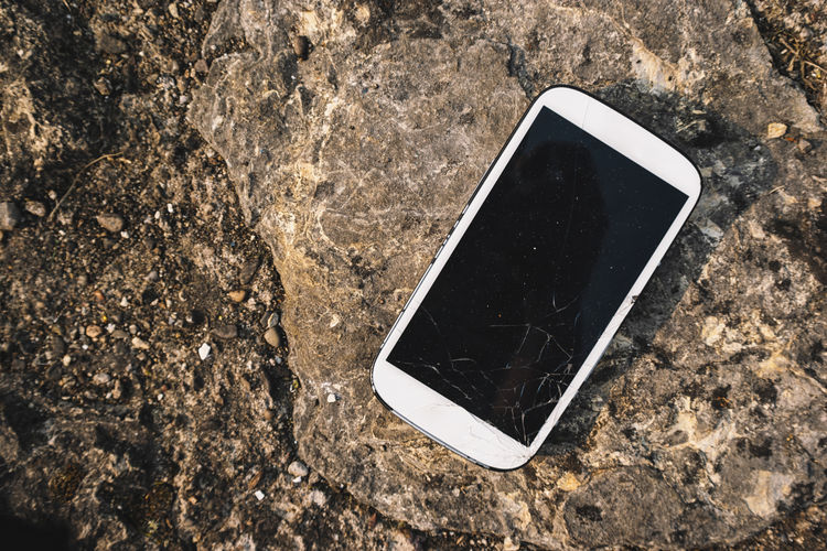 Broken smartphone screen on a stone background Cellphone Destruction Screen Smashed Accient Background Black Broken Cell Communication Conncetion Crack Crushed Damaged Device Display Equipment Glass Mobile Repair Scratched Smart Phone Technology Telephone White Background
