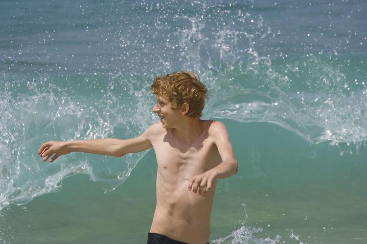 Shirtless Teenage Boy Against Wave Splashing In Sea