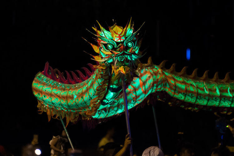 People Carrying Chinese Dragon At Night