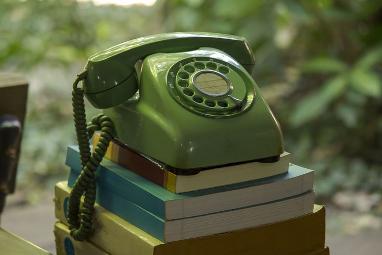 Close-up of rotary phone on stacked books outdoors