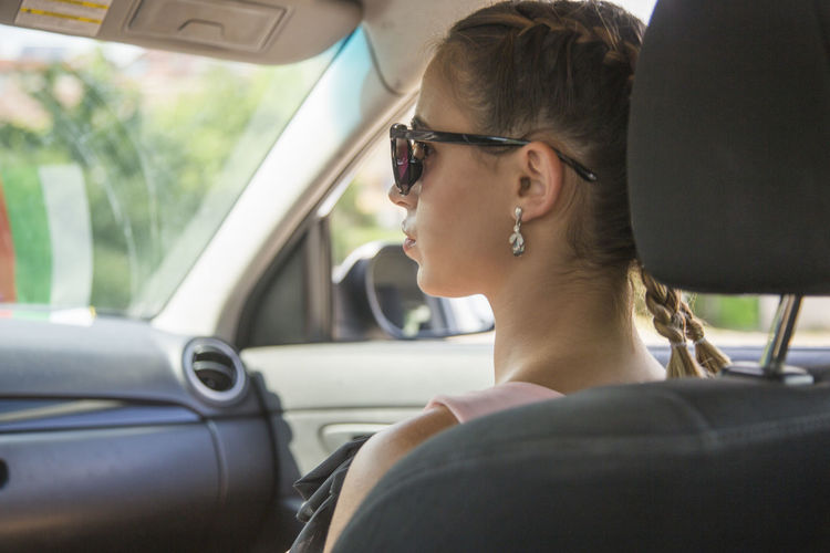 Mode Of Transportation Motor Vehicle Car Transportation Vehicle Interior Real People Land Vehicle Headshot Lifestyles Car Interior Leisure Activity Sunglasses Portrait Young Adult Glasses One Person Women Sitting Travel Day Fashion Outdoors Profile View Teenager