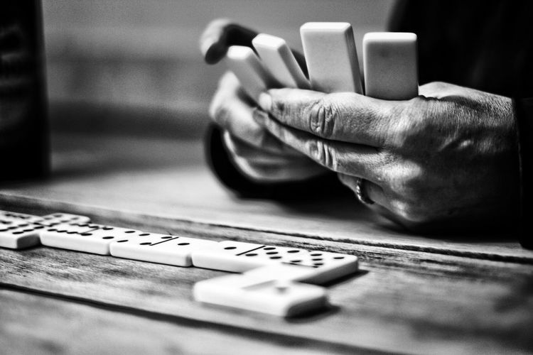 Cropped hands on man playing dominoes on table