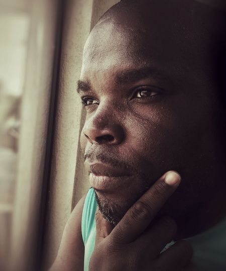 Close-up portrait of man looking through window