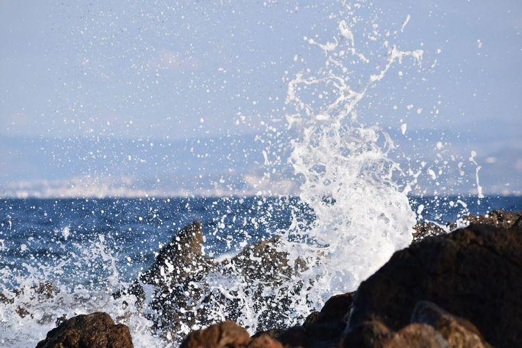 Water splashing in sea against clear sky