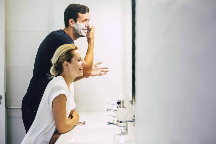 Side view of smiling couple in bathroom