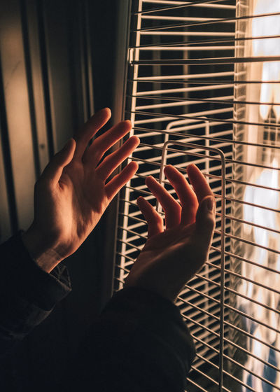 Cropped Hands Against Window At Home