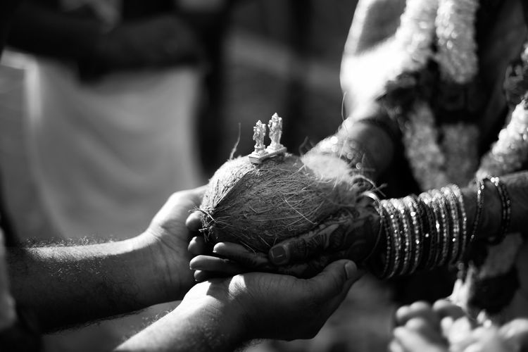 Cropped hands of couple holding coconut during wedding ceremony