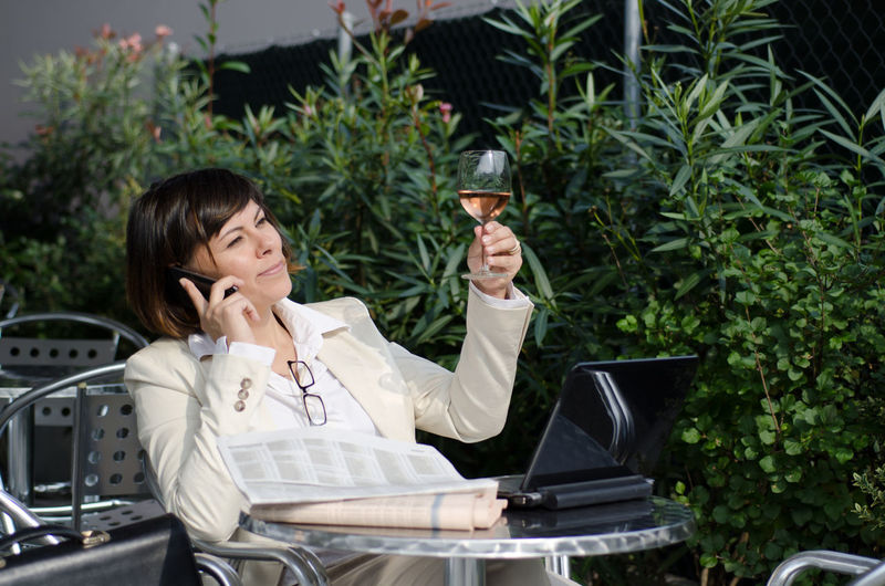 Businesswoman Holding Wineglass While Talking On Mobile Phone