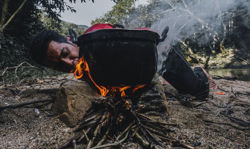 Young man blowing fire while preparing food in forest
