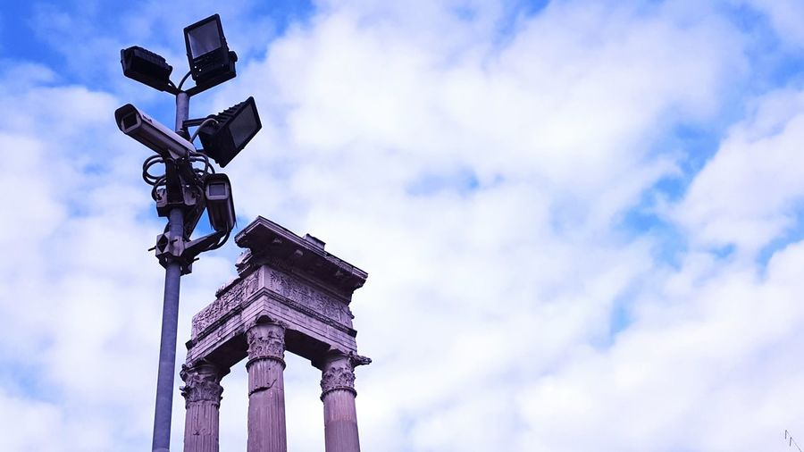 Low angle view of flood light and historic columns against cloudy sky