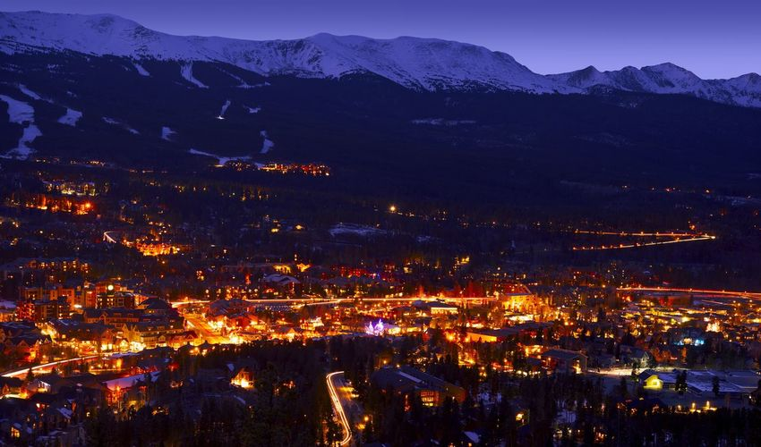 Illuminated townscape against snowcapped mountains