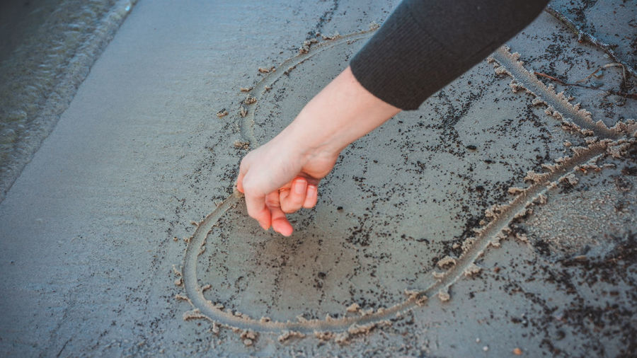 High Angle View Of Hand Drawing Heart Shape On Wet Sand At Beach