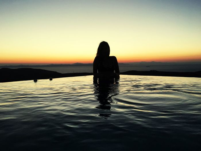 Silhouette woman in infinity pool against sky during sunset