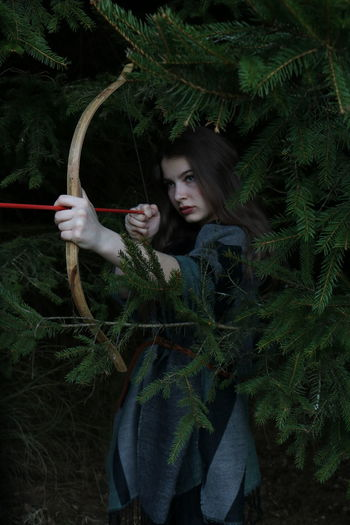 Young woman holding aiming bow while standing in forest