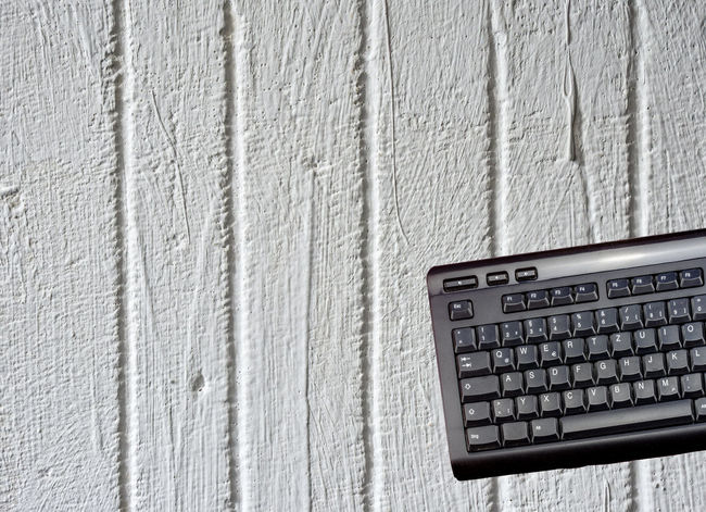 Keyboard of a computer exposed in front of a white painted concrete wall Isolated Wall Abstract Black Close-up Communication Computer Computer Key Computer Keyboard Concrete Concrete Wall Day Expose Indoors  No People Technology White White Background