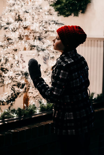 One Person Side View Child Clothing Real People Lifestyles Childhood Standing Hat Boys Leisure Activity Males  Nature Waist Up Plant Tree Winter Men Architecture Warm Clothing Outdoors Profile View Christmas Lights Girl