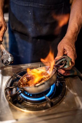 Midsection of man preparing food on stove