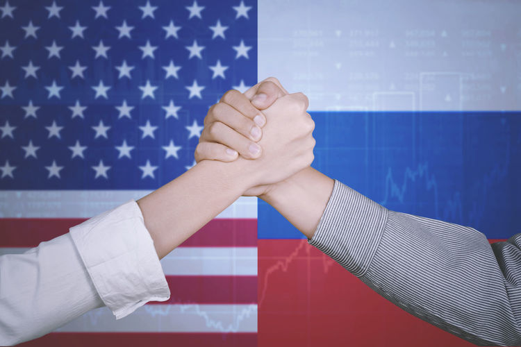 Cropped image of people holding hands against russian and american flags