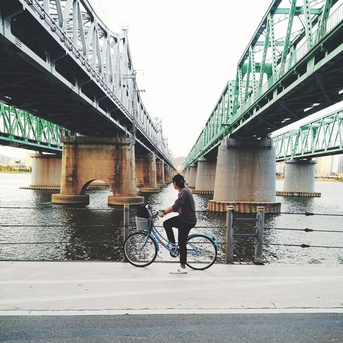 Man riding bicycle on bridge over river in city