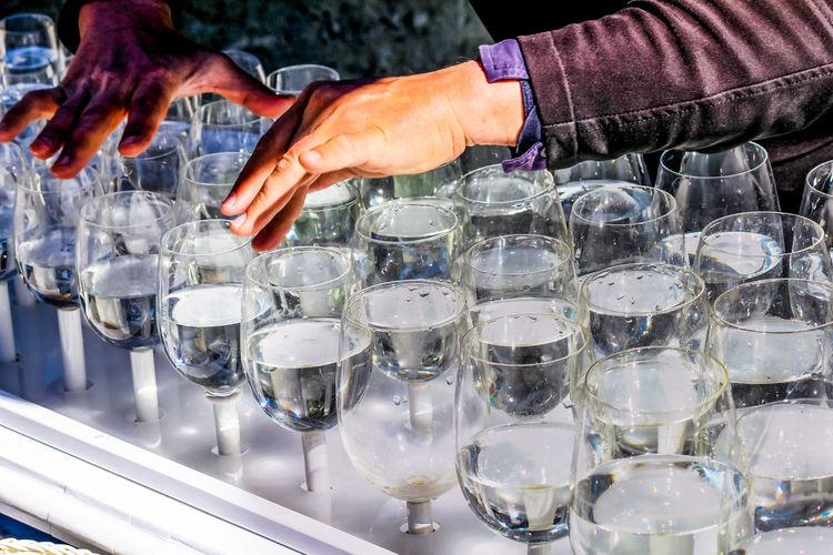 Cropped hands of bartender adjusting glasses at bar