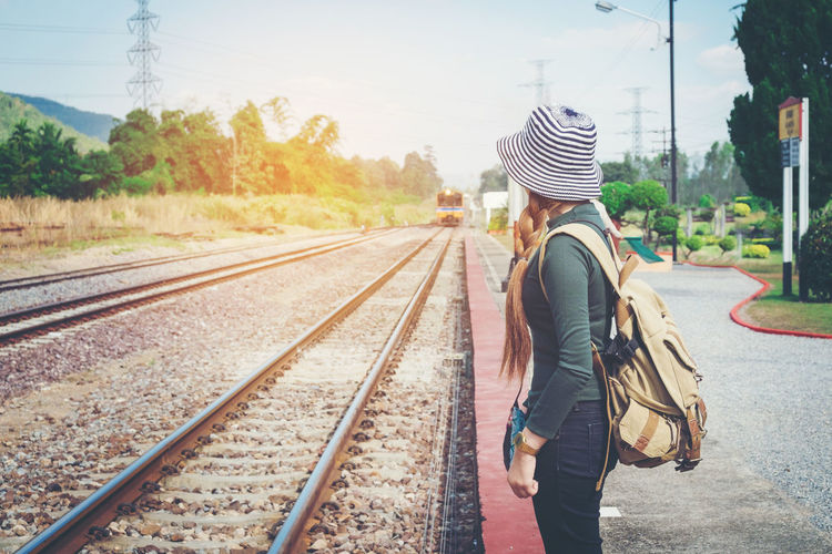 Side View Of Young Woman Waiting On Railroad Station Platform