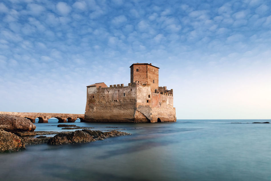 Torre Astura - Italy. An ancient fortified tower overlooking the sea, built on the cliff to the beach and connected by a single bridge. Architecture Beauty In Nature Blue Building Exterior Built Structure Castle Cloud - Sky Day Fort History Medieval Nature No People Non-urban Scene Outdoors Scenics Sea Sky Torre Astura Torreastura Tranquil Scene Water