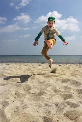 Boy jumping on beach against sky