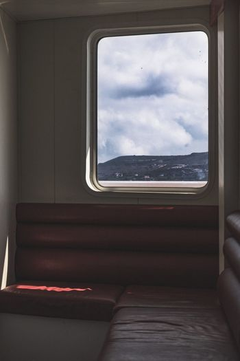 Low angle view of train window against sky