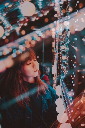 Portrait of girl looking at illuminated lights