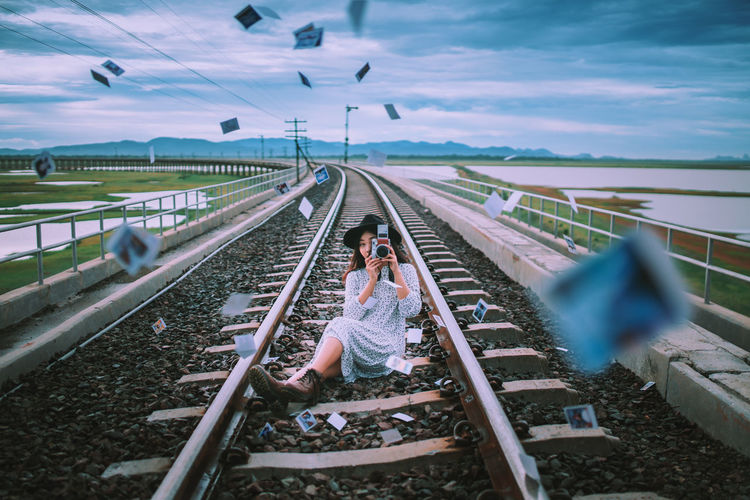 Full length of young woman photographing from camera while sitting amidst instant print transfers on railroad track