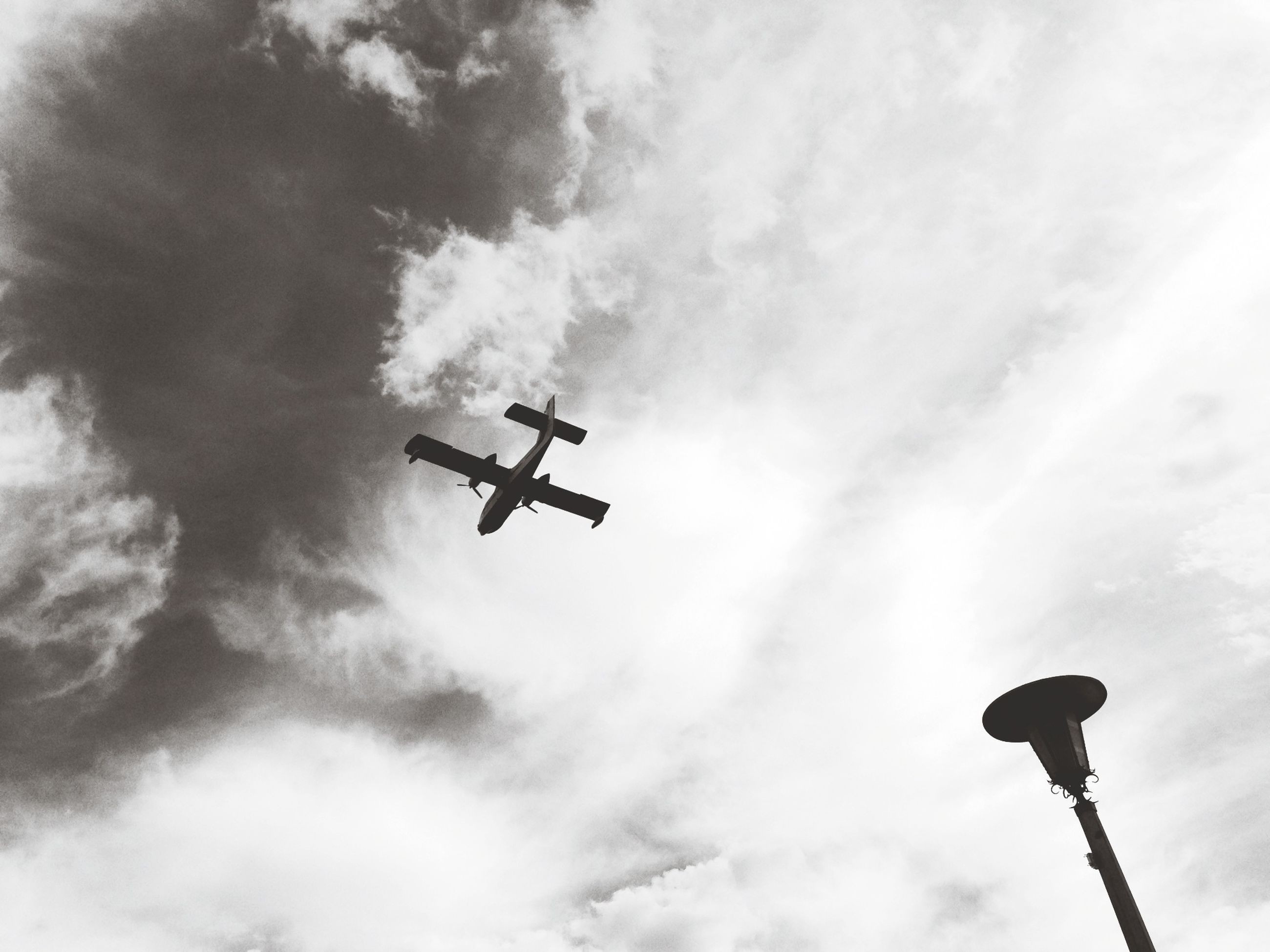 low angle view, airplane, air vehicle, transportation, sky, mode of transport, cloud - sky, flying, street light, cloudy, lighting equipment, mid-air, travel, public transportation, on the move, day, cloud, outdoors, commercial airplane, military airplane