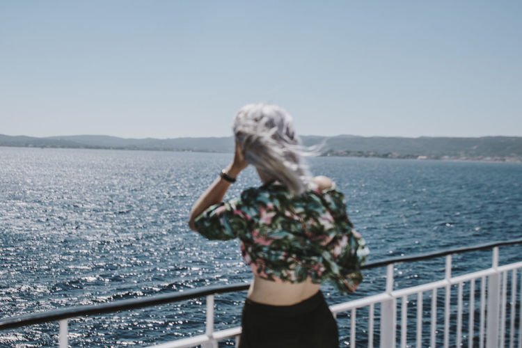 Woman standing by railing against sea against clear sky