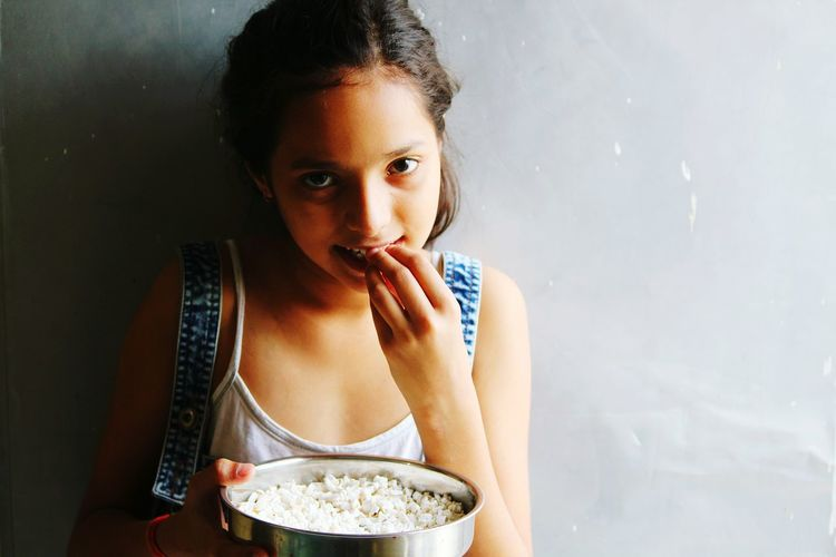 Portrait of girl eating popcorn against wall