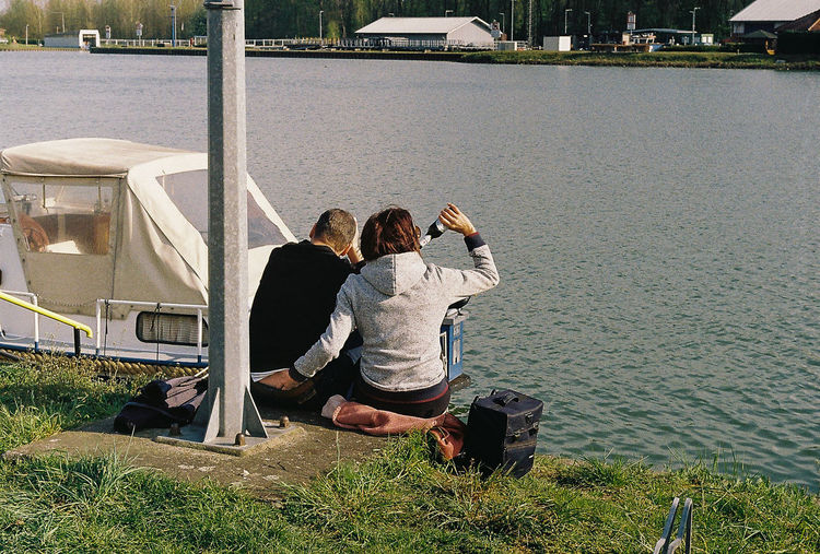 Rear view of couple with umbrella at shore