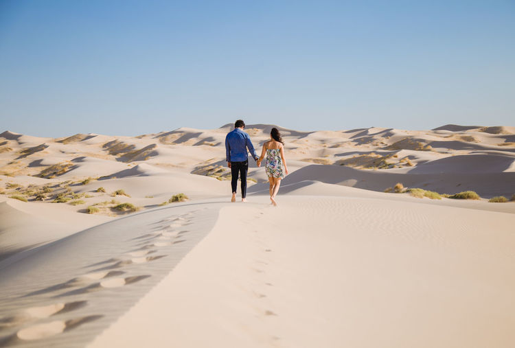 Rear View Of Couple Walking On Sand At Desert Against Sky