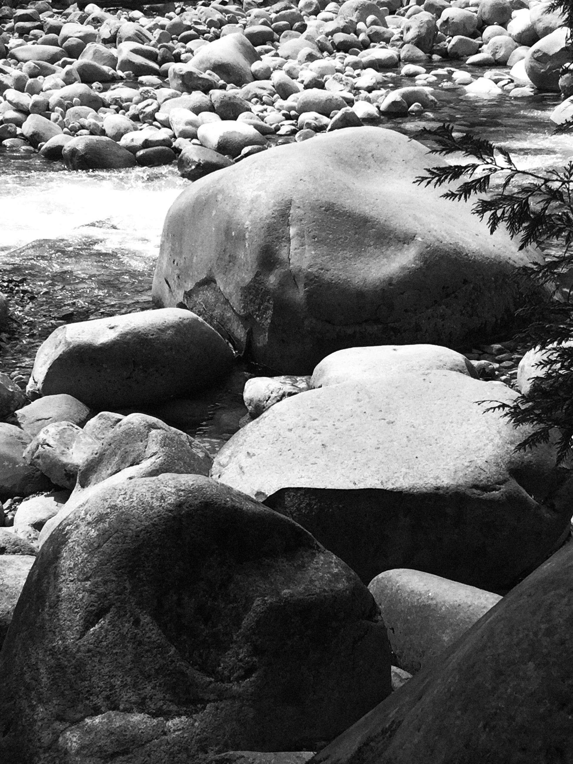rock - object, high angle view, water, nature, stone - object, rock formation, rock, day, sunlight, tranquility, outdoors, beauty in nature, beach, stone, sand, shadow, no people, shore, tranquil scene, river