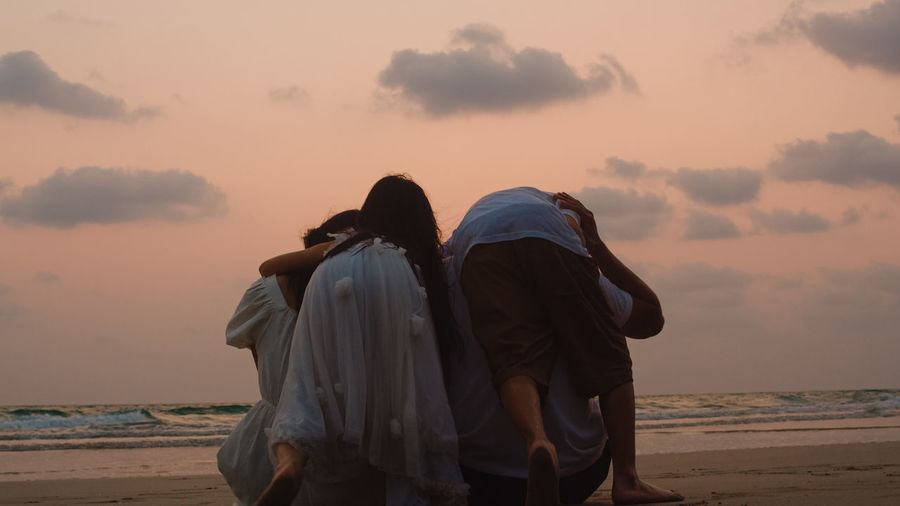 Rear view family at beach against sky during sunset