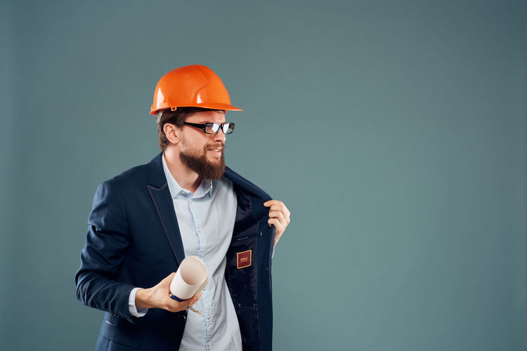 Man holding hat against gray background