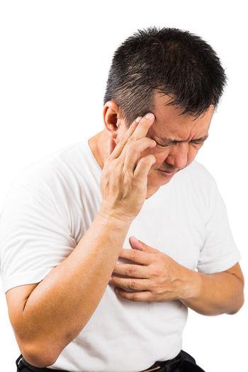 Asian man suffering with migraine headache Asian  Stress Depression - Sadness Emotion Hand Headache Mature Adult Men One Person Studio Shot Waist Up White Background