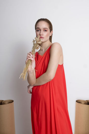 Portrait of beautiful young woman holding crop against white background