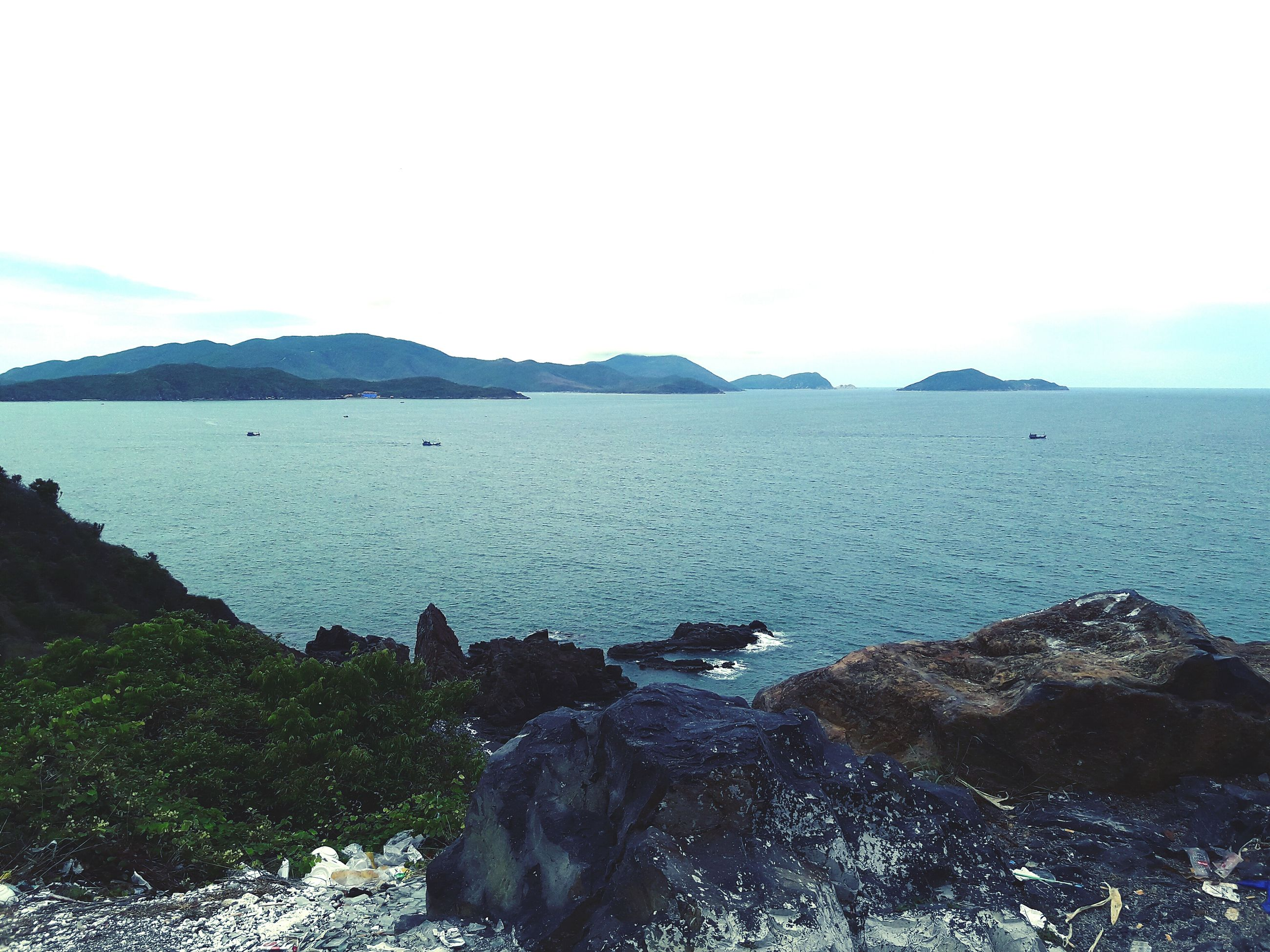 water, mountain, scenics, tranquil scene, tranquility, beauty in nature, sea, clear sky, nature, rock - object, copy space, mountain range, idyllic, sky, non-urban scene, remote, outdoors, coastline, day, landscape