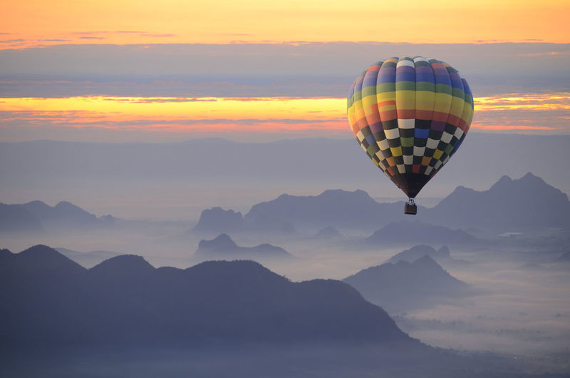 Hot air balloon over the sea of mist. Hot Air Balloon Balloon Air Vehicle Sky Mountain Scenics - Nature Beauty In Nature Mid-air Sunset Flying Adventure Transportation Non-urban Scene Nature Cloud - Sky Multi Colored Tranquil Scene Mode Of Transportation Travel Tranquility Mountain Range Ballooning Festival No People Outdoors