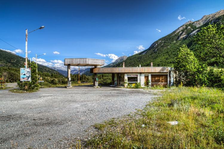 old gas station Abandoned Abandoned Buildings Abandoned Places Blue Built Structure Clear Sky Day Empty Gas Station Grass Landscape Mountain Mountain Range Nature Old Plant Road Sky Street Street Light The Way Forward Tranquil Scene Tranquility Transportation Tree