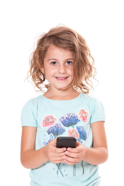 Young girl using smart phone. All on white background. Cell Phone  Child Childhood Curly Hair Girl Girlhood Isolated On White Isolated White Background Kid Mobile Phone One Person Smart Phone Studio Shot Text Message Text Messaging White Background Young Girl
