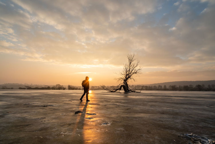Man standing on frozen lake against sky during sunset