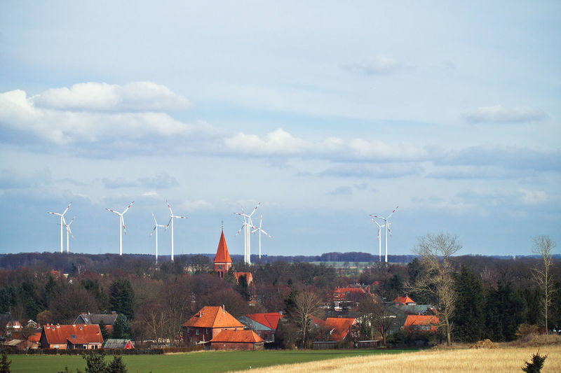 Wind Turbines On Grassy Field And Town Against Sky