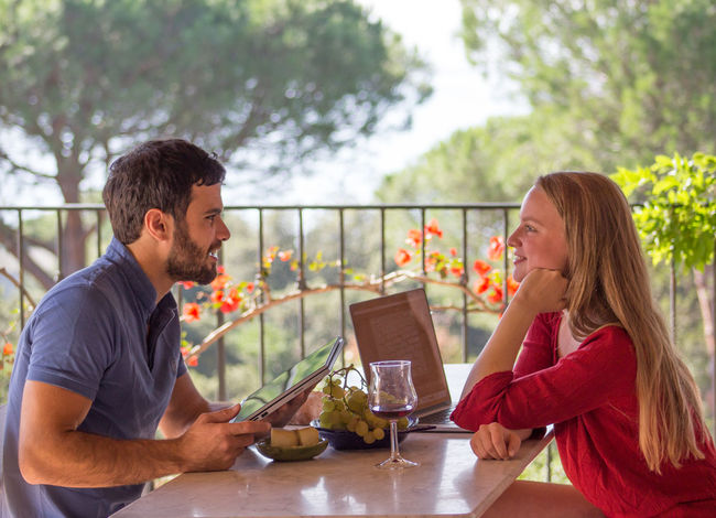 Young couple engaged in conversation Beautiful Background Adult Cheerful Conversation Day Enjoying Each Others Company Enjoyment Flowers Food And Drink Friendship Laptops Mid Adult Millennials Outdoors People Side View Sitting Smiling Table Togetherness Two People Waist Up Young Adult Young Man Young Woman