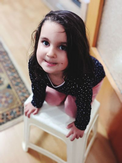 Portrait of smiling girl sitting on table at home