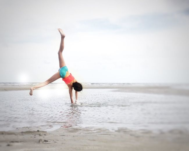 Rear view of girl doing cartwheel on shore at beach against sky
